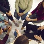 Gruppe steht zusammen und hält sich an den Händen